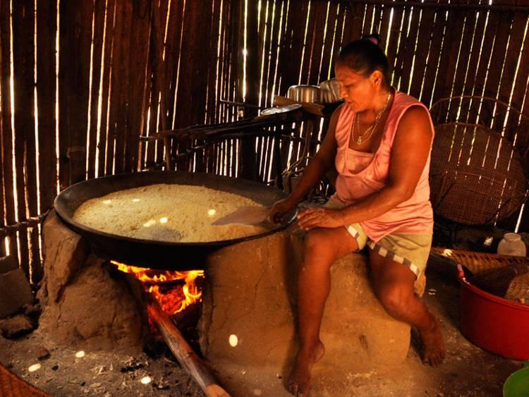 Lucinda García uses a large clay pan to toast manioc into the popular mañoco. (Juan Carlos Rocha for Infosurhoy.com)