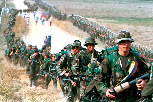 Leftist rebels of the Revolutionary Armed Forces of Colombia (FARC) patrol by a roadway near to San Vicente de Caguan, Caqueta province, Colombia, January 9. 1999.  REUTERS/ Jose Miguel Gomez/File Photo  - RTX2HPEB