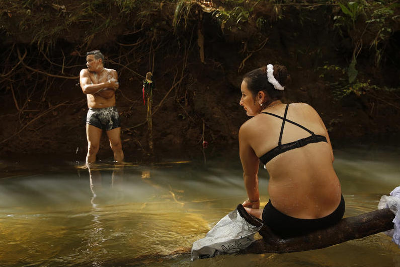 "Revolutionary Armed Forces of Colombia member Viviana, 28, and her comrade Jon, 34, bathe in spring waters by their camp. ""We're all kids of the same town and we've been killing each other,"" Viviana says regarding the long war in the region between the FARC and paramilitary forces."