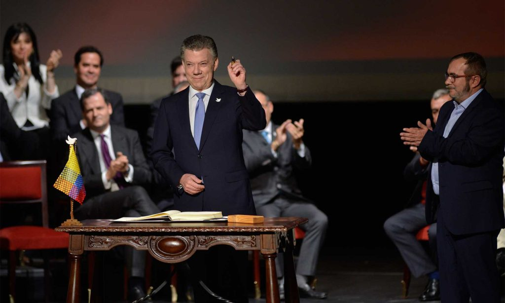 "Presidente Juan Manuel Santos holds the ""pen"" used to sign the new deal, the ""Nuevo Acuerdo de Paz para Colombia"". The leader of the FARC, Rodrigo Londoño looks on during the ceremony Thursday morning in the Teatro Colón de Bogotá"