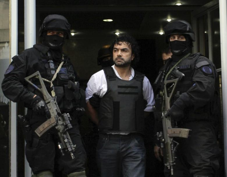 Argentine policemen escort Henry de Jesus Lopez Londono, alleged leader of a Colombian drug trafficking outside a courthouse in Buenos Aires October 31, 2012. REUTERS/Stringer