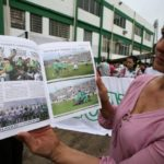 A fan of Chapecoense soccer team shows a magazine of the team in front of the Arena Conda stadium in Chapeco